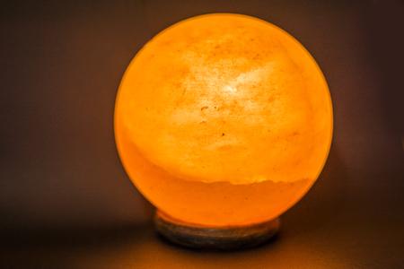 The Lamp Placed Inside Of The Salt Stone. Horizontal Indoors Shot Of  Himalayan Salt Round