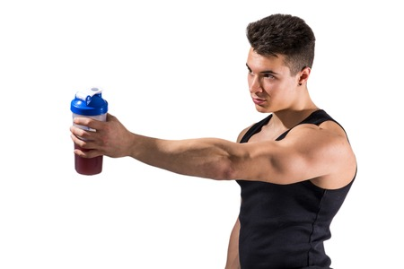 Muscular young male bodybuilder holding protein shake bottle, drinking. Isolated on white