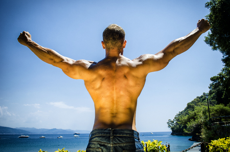 beach hunk: Back of young muscle man at the seaside, outdoors, showing muscular back and shoulders in front of the sea