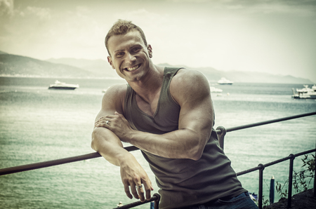 beach hunk: Handsome young muscle man at the seaside, outdoors, in front of the sea Stock Photo