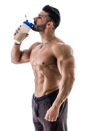 Handsome muscular man posing with protein blender in his hands, drinking from it, isolated on white background. Stock Photo