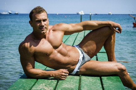 Attractive young, athletic muscle man sitting on a wood pier, looking at camera