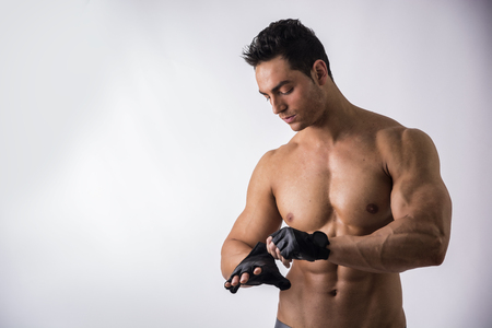 half naked: Half Body Shot of a Topless Muscled Man Wearing Black Gloves for Workout on Light Background. Stock Photo