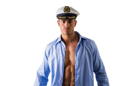 Muscular male sailor with open shirt on muscle torso, wearing marine hat, isolated on white