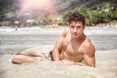 プーケット島、タイ、上半身裸でビーチに横たわるハンサムな若い男ボクサー パンツを着ては、筋肉フィット体を見せ、カメラ目線 写真素材