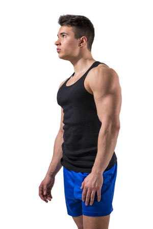 Handsome young muscular man looking up to a side in studio shot, isolated on white background