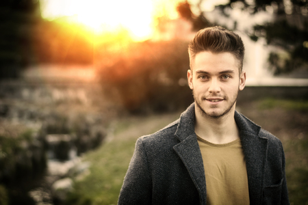 Handsome young man standing in city park, looking confident and relaxed in autumn or spring evening