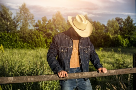 Portrait of farmer or cowboy in hat with unbuttoned shirt on muscular torso, looking down, while standing next to hay field in countryside