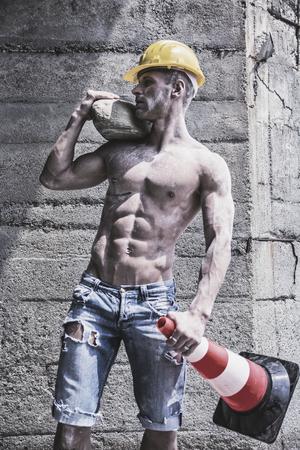 Gespierde knappe bouwvakker staande shirtless in de voorkant van een betonnen muur, op zoek weg naar een kant