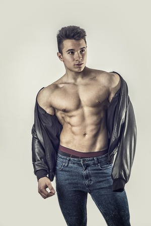 Handsome young muscular man shirtless wearing jeans, on grey background in studio shot Фото со стока