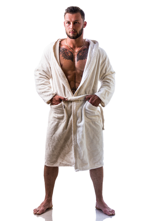 Handsome young muscle man wearing white bathrobe, keeping it open on muscular torso and pecs, isolated on white background Stock Photo