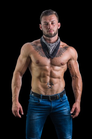 Handsome shirtless muscular man with jeans and black bandanna around his neck, standing, isolated on black background Stock Photo
