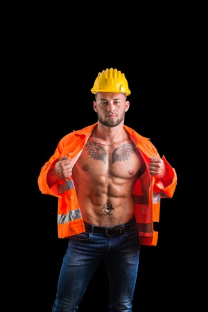 Handsome young muscular construction worker with orange suit open on naked torso, isolated on black background in studio Stock Photo
