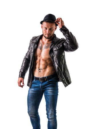 Muscular man with leather jacket on naked torso, wearing fedora hat, isolated on white background in studio