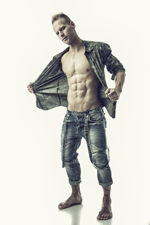 Good Looking Young Gym Fit Man Showing His Sexy Six Pack Abs While Looking at the Camera. Isolated on White Background. Stock Photo