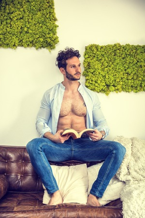 Shirtless sexy male model lying alone on couch in his living-room, looking at camera with a seductive attitude, reading a book,, with shirt open on muscular chest and torso Banque d'images