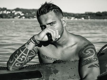 Séduisante jeune homme sportif torse nu, debout dans l'eau de mer ou de lac, porte des shorts, regardant la caméra Banque d'images - 91895008
