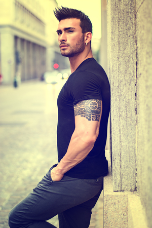 Handsome muscular man with tattoo posing in European city center, Turin, Italy