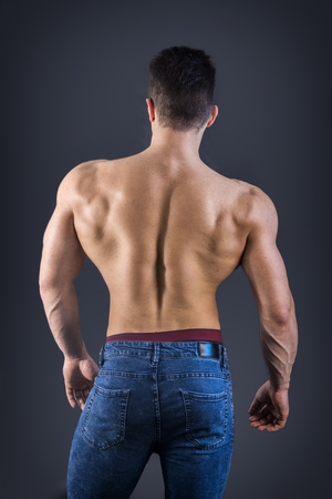 Back of young muscular man shirtless wearing jeans, on dark background in studio shot