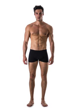 Hübscher hemdloser muskulöser Mann, stehend, in der Atelieraufnahme und betrachten die Kamera, lokalisiert auf Weiß