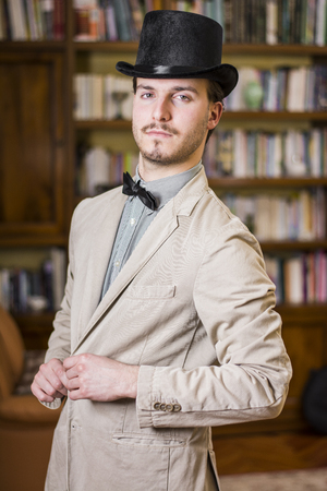 Attractive young man wearing top hat and bow tie, looking at camera. Indoors shot Stock Photo