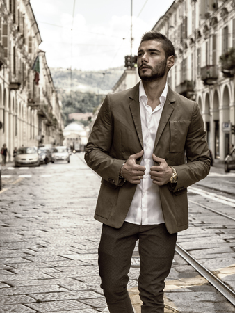 Attractive man outdoor wearing elegant jacket, in European city, Turin in Italy Stock Photo