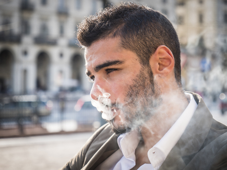 Attractive man outdoor wearing elegant jacket, in European city, Turin in Italy, smoking a cigarette
