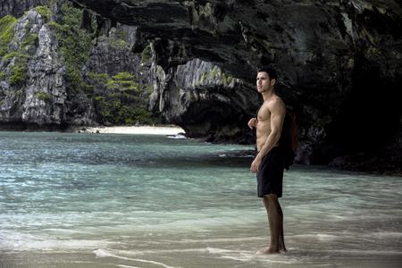 Giovane bello che sta su una spiaggia nell'isola di Phuket, Tailandia, shorts senza pugile d'uso senza camicia, mostranti corpo adatto muscolare Archivio Fotografico - 97929249