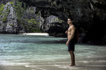 Handsome young man standing on a beach in Phuket Island, Thailand, shirtless wearing boxer shorts, showing muscular fit body Stockfoto