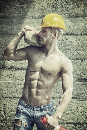 Handsome muscular construction worker standing shirtless in front of a concrete wall, looking away to a side Banque d'images