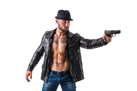 Handsome man wearing leather jacket on naked muscular torso pointing gun to a side, isolated on white background