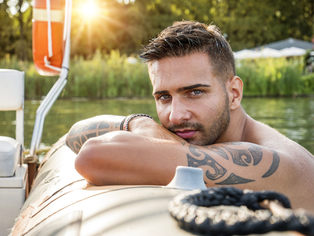 Portrait of young bearded handsome man with tattooed body looking sexually at camera sailing in boat.