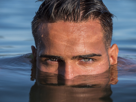 Attractive young shirtless athletic man standing in water in sea or lake, with half face submerged underwater, looking at camera Banque d'images