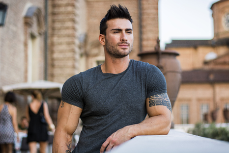 Attractaive muscular man with tattoo posing in European city center, Turin, Italy, looking at camera