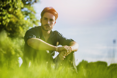 Attractive, fit young man relaxing sitting on lawn in the countryside among grass, looking at camera Stock Photo