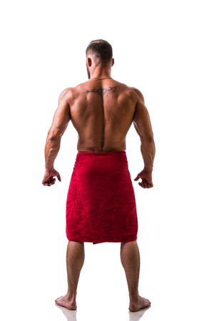 Back of shirtless muscular man, standing, in studio shot with towel around his waist, isolated on white. Full length shot