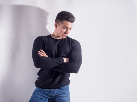 Handsome young muscular man looking down in studio shot, on grey background in studio Standard-Bild