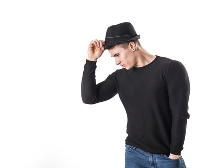 Handsome young muscular man looking down in studio shot, wearing fedora hat, isolated on white background