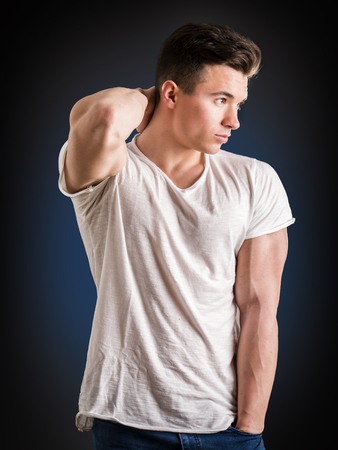 Handsome young muscular man looking down to a side, in studio shot over neutral dark background Standard-Bild