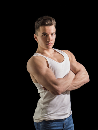 Handsome young muscular man looking at camera, in studio shot over neutral dark background