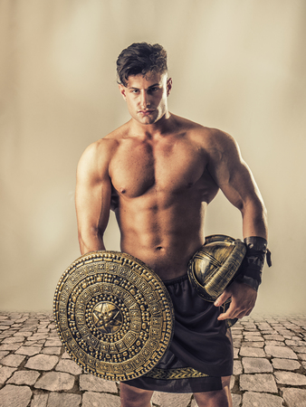 Young handsome muscular man posing in roman or spartan gladiator costume with shield, helmet and sword, on neutral background in studio Фото со стока
