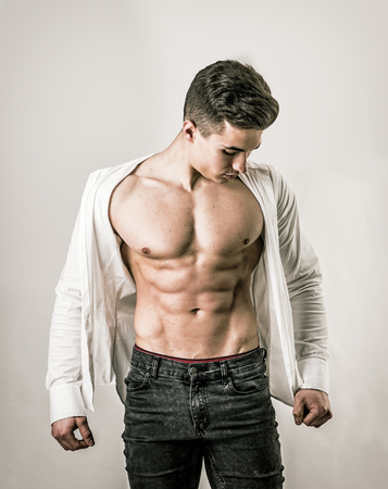 Handsome young muscular man shirtless wearing jeans, taking off white shirt on muscle torso, on light background in studio shot