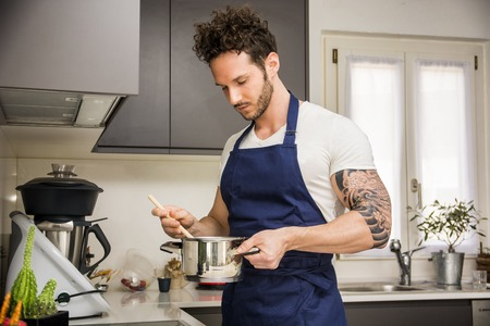 Handsome muscular man in kitchen at home, cooking at the stove