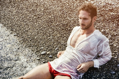 Handsome muscular man on the beach lying on gravel, wearing wet white shirt
