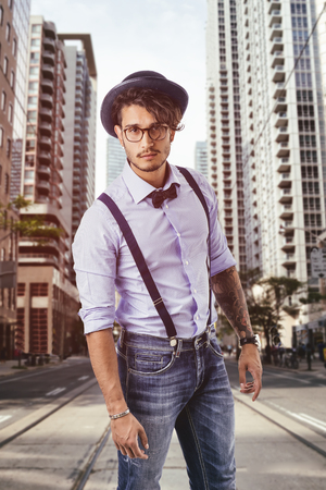 Portrait of hipster looking at camera in the street, wearing hat, glasses, bow-tie and suspenders looking at camera Standard-Bild