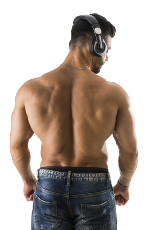 Back of shirtless muscular bodybuilder man listening to music with headphones, isolated on white background Standard-Bild