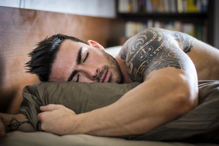 Hemdloses muskulöses männliches Model, das allein auf dem Bett in seinem Schlafzimmer schläft und sich ausruht
