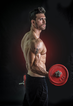 Muscular sexy shirtless man exercising biceps with dumbbells, on dark background
