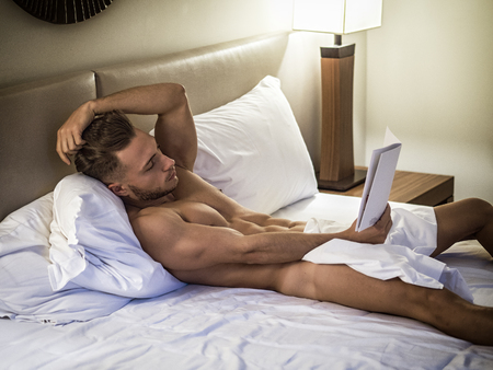 Young shirtless muscular man lying in bed and reading a book Standard-Bild - 116235742
