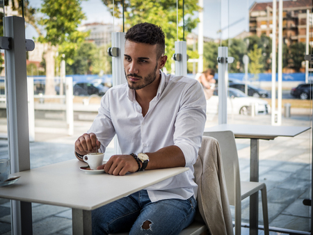 Attractive Young Man Drinking Coffee while Sitting in a Bar with Serious Expression